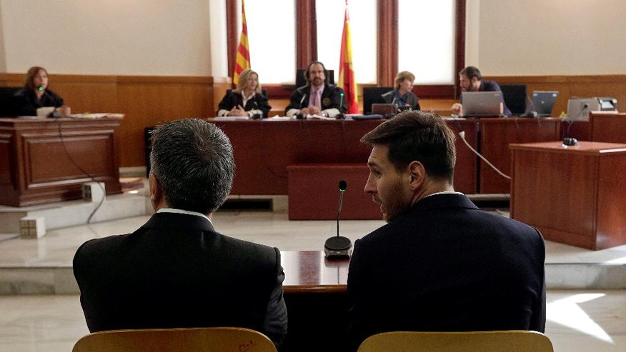 Barcelona's Lionel Messi, right, and his father Jorge Horacio Messi sit in court in Barcelona, Spain, Thursday June 2, 2016. Lionel Messi denied having knowledge of the tax issues that led to fraud charges against him, saying Thursday he signed documents without reading them because he trusted his father and the advisers responsible for managing his finances. (Alberto Estevez/Pool photo via AP)