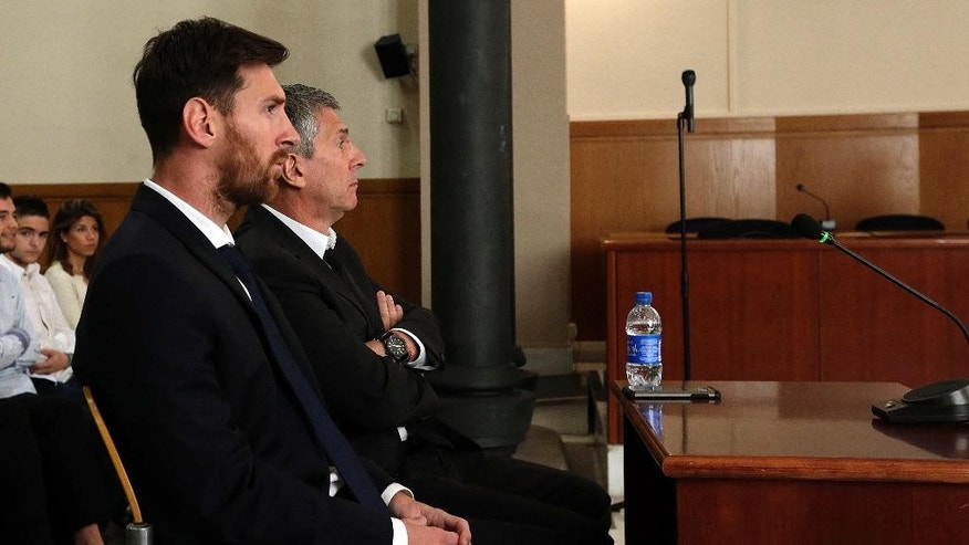 Barcelona's Lionel Messi, foreground, and his father Jorge Horacio Messi sit in court in Barcelona, Spain, Thursday June 2, 2016. Lionel Messi denied having knowledge of the tax issues that led to fraud charges against him, saying Thursday he signed documents without reading them because he trusted his father and the advisers responsible for managing his finances. (Alberto Estevez/Pool photo via AP)