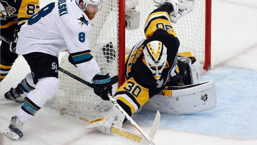 Pittsburgh Penguins goalie Matt Murray (30) pokes the puck away from San Jose Sharks' Joe Pavelski (8) during the third period in Game 2 of the NHL hockey Stanley Cup Finals on Wednesday, June 1, 2016, in Pittsburgh. (AP Photo/Gene J. Puskar)