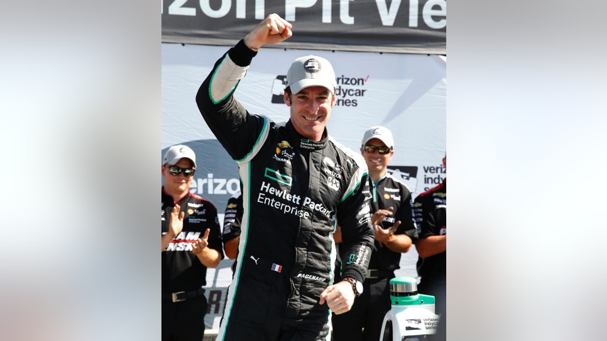Simon Pagenaud, of France, celebrates after winning the pole position in qualifications for race one of the IndyCar Detroit Grand Prix auto racing double header on Belle Isle in Detroit, Friday, June 3, 2016. (AP Photo/Paul Sancya)
