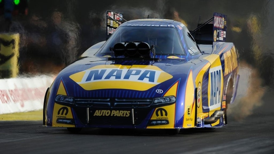 In this photo submitted by the NHRA, Funny Car racer Ron Capps races to the qualifying lead at the NHRA New England Nationals with a run of 3.865 seconds at 325.92 mph. His elapsed time is the second quickest Funny Car pass in NHRA history and a track record at New England Dragway located an hour outside of Boston. (Marc Gewertz/NHRA/National Dragster via AP) MANDATORY CREDIT