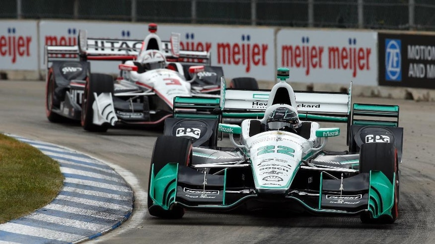 Simon Pagenaud (22) leads Helio Castroneves into a turn during race one of the IndyCar Detroit Grand Prix auto racing doubleheader on Belle Isle in Detroit, Saturday, June 4, 2016. (AP Photo/Paul Sancya)
