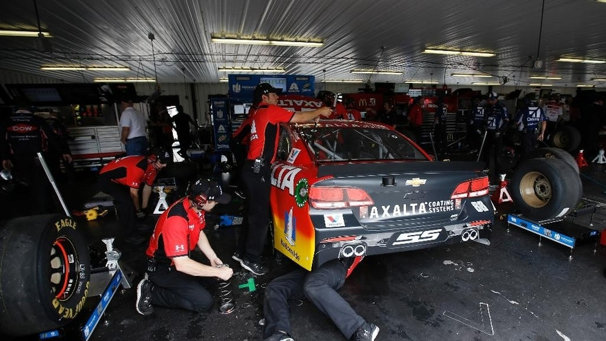 Crew members work on the car of Dale Earnhardt Jr. during a practice session for Sunday's NASCAR auto race, Saturday, June 4, 2016, in Long Pond, Pa. (AP Photo/Matt Slocum)