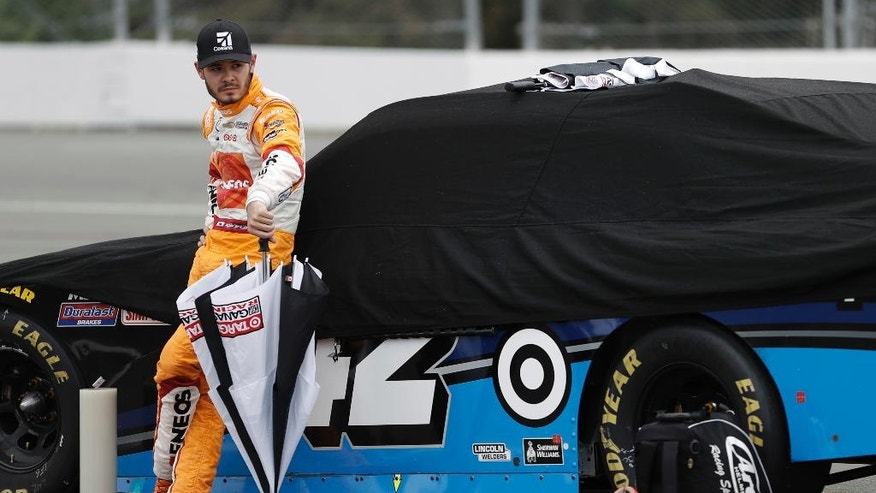 Kyle Larson stands with his car during a rain delay in the NASCAR Xfinity series auto race at Pocono Raceway, Saturday, June 4, 2016, in Long Pond, Pa. (AP Photo/Matt Slocum)