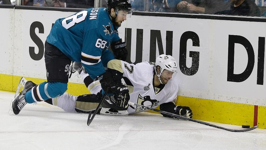 Pittsburgh Penguins center Matt Cullen (7) reaches for the puck under San Jose Sharks right wing Melker Karlsson (68), from Sweden, during the first period of Game 3 of the NHL hockey Stanley Cup Finals in San Jose, Calif., Saturday, June 4, 2016. (AP Photo/Marcio Jose Sanchez)