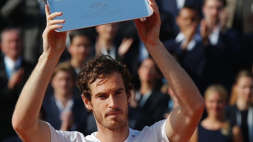 Britain's Andy Murray holds the runner-up trophy after losing the final of the French Open tennis tournament against Serbia's Novak Djokovic in four sets 3-6, 6-1, 6-2, 6-4, at the Roland Garros stadium in Paris, France, Sunday, June 5, 2016. (AP Photo/Michel Euler)