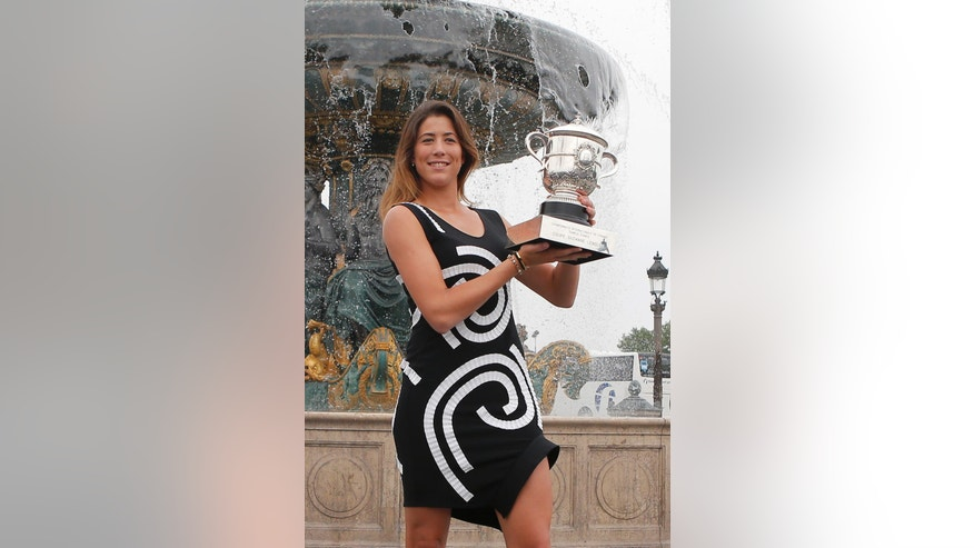 Spain's Garbine Muguruza poses with the cup during a photocall at Concorde Plaza in Paris, Sunday June, 5 2016. Muguruza defeated Serena Williams of the U.S. in their final match of the French Open tennis tournament at the Roland Garros stadium. (AP Photo/Francois Mori)