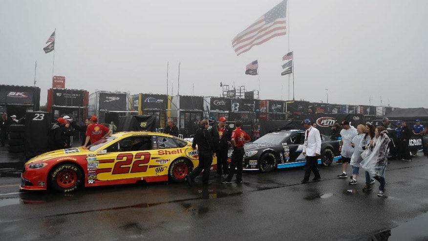 Crew members wait with their cars for an inspection before the NASCAR Sprint Cup series auto race, Sunday, June 5, 2016, in Long Pond, Pa. (AP Photo/Matt Slocum)