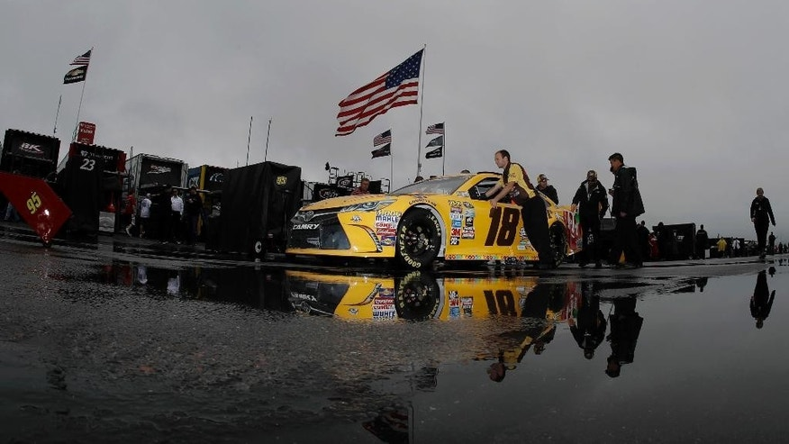Crew members push the car of Kyle Busch in the garage area before the NASCAR Sprint Cup series auto race, Sunday, June 5, 2016, in Long Pond, Pa. (AP Photo/Matt Slocum)