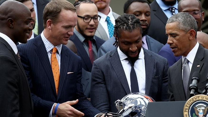 WASHINGTON, DC - JUNE 06: U.S. President Barack Obama is presented with a Denver Broncos helmet by quarterback Peyton Manning while welcoming the National Football League Super Bowl champion Denver Broncos to the White House Rose Garden on June 6, 2016 in Washington, DC. The Broncos defeated the Carolina Panthers 24-10 in Super Bowl 50. (Photo by Win McNamee/Getty Images)