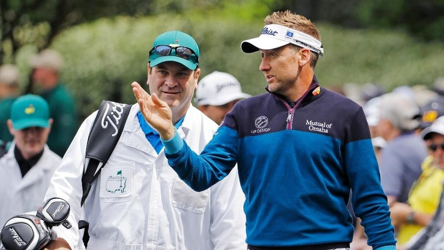 FILE - A Wednesday, April 6, 2016 photo from files showing Ian Poulter, of England, walking to the ninth tee with his caddie during the par three competition at the Masters golf tournament in Augusta, Ga. Ian Poulter will serve as a vice captain of Europe's Ryder Cup team after a foot injury ended his chances of playing. Facing four months on the sidelines, Poulter joins Thomas Bjorn, Paul Lawrie and Padraig Harrington as one of captain Darren Clarke's four assistants.(AP Photo/David J. Phillip, File)