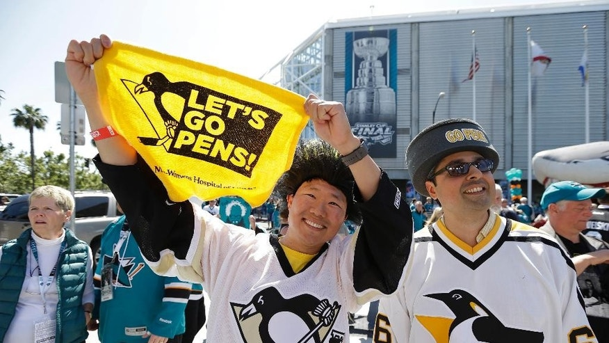 Thad Hwang, left, and Angelo Puglisi, right, both of San Francisco, watch a live broadcast outside SAP Center before the start of Game 4 of the NHL hockey Stanley Cup Finals between the San Jose Sharks and Pittsburgh Penguins in San Jose, Calif., Monday, June 6, 2016. (AP Photo/Eric Risberg)