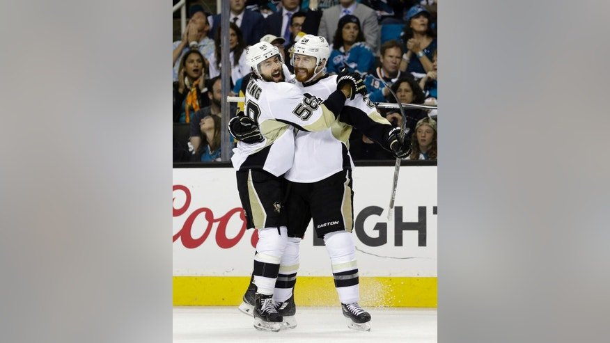 Pittsburgh Penguins' Ian Cole, right, celebrates with Kris Letang (58) after scoring a goal against the San Jose Sharks during the first period of Game 4 of the NHL hockey Stanley Cup Finals, Monday, June 6, 2016, in San Jose, Calif. (AP Photo/Ben Margot)
