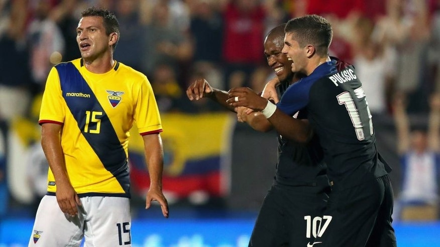 FRISCO, TX - MAY 25: Pedro Larrea #15 of Ecuador reacts as Darlington Nagbe #10 of the United States celebrates with Christian Pulisic #17 of the United States after scoring against Ecuador during an International Friendly match at Toyota Stadium on May 25, 2016 in Frisco, Texas. (Photo by Tom Pennington/Getty Images)