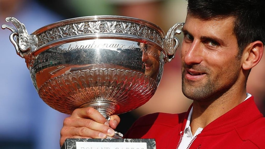 Serbia's Novak Djokovic holds the trophy after winning the final of the French Open tennis tournament against Britain's Andy Murray in four sets 3-6, 6-1, 6-2, 6-4, at the Roland Garros stadium in Paris, France, Sunday, June 5, 2016. (AP Photo/Christophe Ena)