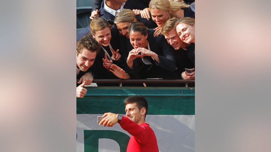 Serbia's Novak Djokovic takes a selfie with stadium hostesses after winning the final of the French Open tennis tournament against Britain's Andy Murray in four sets 3-6, 6-1, 6-2, 6-4, at the Roland Garros stadium in Paris, France, Sunday, June 5, 2016. (AP Photo/Michel Euler)