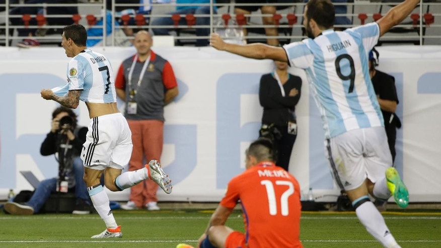 Argentina's Angel Di Maria, right, celebrates after scoring against Chile as Chile's Gary Medel, center, sits on the ground and Argentina's Gonzalo Higuain, right, celebrates during a Copa America Centenario Group A soccer match at the Levi's Stadium in Santa Clara, Calif., Monday, June 6, 2016. (AP Photo/ Marcio Jose Sanchez)