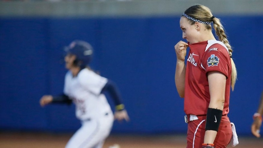 Oklahoma pitcher Jayden Chestnut, right, watches as Auburn's Kasey Cooper rounds the bases on her two-run home run in the fourth inning of the second game of the best-of-three championship series in the NCAA softball Women's College World Series in Oklahoma City, Tuesday, June 7, 2016. (AP Photo/Sue Ogrocki)