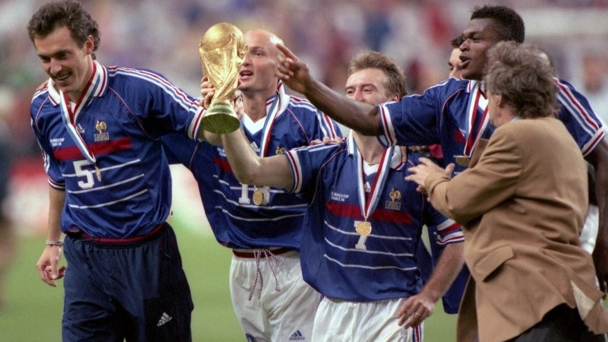 FILE - In this July 12, 1998 filer, Didier Deschamps, center, celebrates on the pitch with the world cup after defeating Brazil in the World Cup Final, in Stade de France, in Saint-Denis, Paris. (AP Photo/ Eric Draper, File)