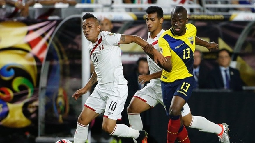 Peru's Christian Cueva dribbles the ball away from Ecuador's Enner Valencia on June 8, 2016, in Glendale, Ariz.