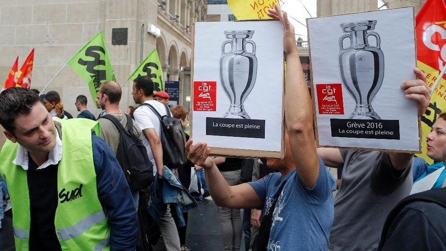 "French railway workers and Labor unions members hold posters depicting the Euro 2016 trophy, during a demonstration against the French government and labor law reforms at Gare Du Nord Station in Paris France, Wednesday June 8, 2016. Workers of France's national rail service demonstrate as part of months of protests over changes to labor protections. Banners with the Cup read: ""2016 strike: the cup is full"" referring to a French expression meaning that someone is disgruntled. (AP Photo/Francois Mori)"