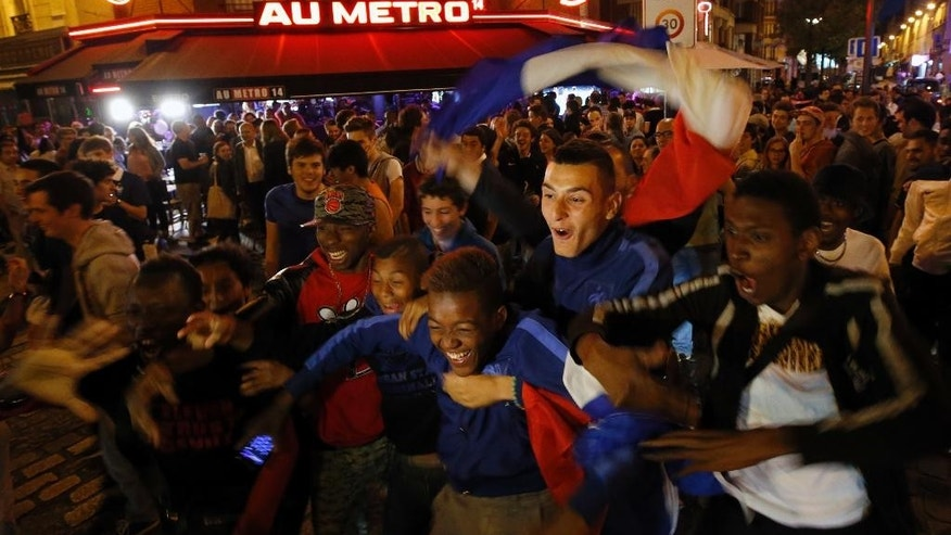 FILE- In this Friday, June 20, 2014 file photo, French soccer supporters react as they watch a live broadcast of the group E World Cup soccer match between Switzerland and France, outside of the Metro 14th District bar in Paris, France. Bar and restaurants owners won't be allowed to set up TV screens outside their businesses during the European soccer championship. The move is aimed at improving security during the tournament, with French authorities expecting fewer people will gather if outdoor screens are banned.  (AP Photo/Francois Mori, File)