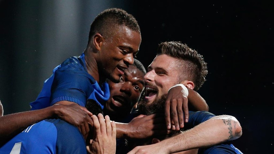 France's Olivier Giroud, right, celebrates after scoring with teammate Paul Pogba, center, and Patrice Evra, left, during the friendly soccer match between France and Scotland at the Saint Symphorien Stadium in Metz, eastern France, Saturday, June 4, 2016. The French squad is in preparation for the EURO 2016 soccer championships which will start on June 10, 2016. (AP Photo/Thibault Camus)