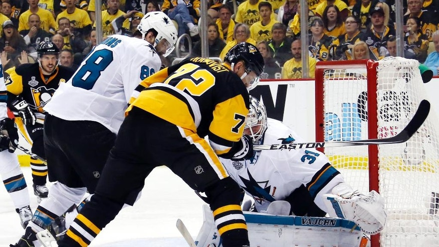 San Jose Sharks goalie Martin Jones (31) turns a shot away as Pittsburgh Penguins' Patric Hornqvist (72) and Sharks' Brent Burns (88) scramble in front of the net during the third period in Game 5 of the NHL hockey Stanley Cup Finals on Thursday, June 9, 2016, in Pittsburgh. (AP Photo/Keith Srakocic)