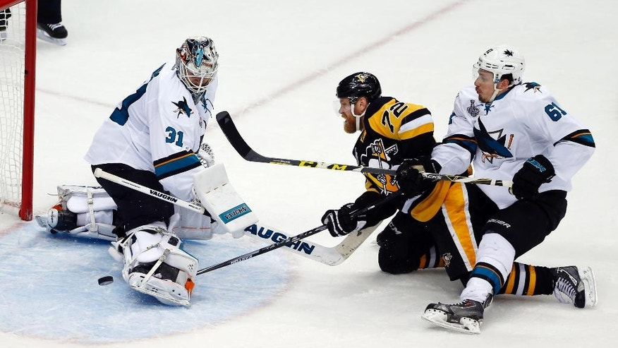 San Jose Sharks goalie Martin Jones (31) turns away a shot by Pittsburgh Penguins' Patric Hornqvist (72) as Sharks' Justin Braun (61) defends during the second period in Game 5 of the NHL hockey Stanley Cup Finals on Thursday, June 9, 2016, in Pittsburgh. (AP Photo/Gene J. Puskar)