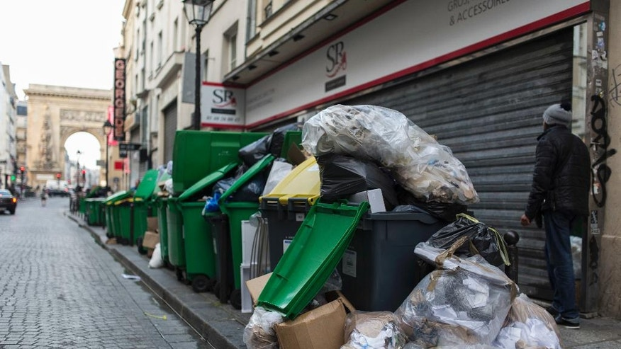 A man walks past a pile of rubbish bags in Paris, France, in Paris, France, Wednesday June 8, 2016. After a rough couple of months which have included protests, fuel shortages, rail strikes and once-in-a-generation floods, France's capital is facing a new challenge : Piles of uncollected trash. A new wave of strikes is disrupting trash collection in Paris with only two days to go until the European Championship soccer tournament, a sporting event predicted to draw 2.5 million spectators. (AP Photo/Kamil Zihnioglu)