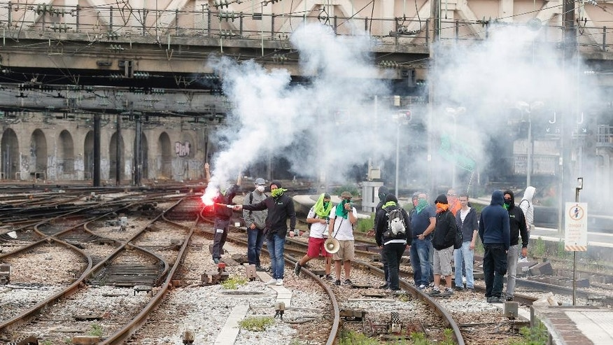 French railway workers and Labor unions members stand with flare on railway tracks at Gare de L'Est station during a demonstration against the French government and labor law reforms in Paris France, Wednesday June 8, 2016. Workers of France's national rail service demonstrate as part of months of protests over changes to labor protections. (AP Photo/Francois Mori)