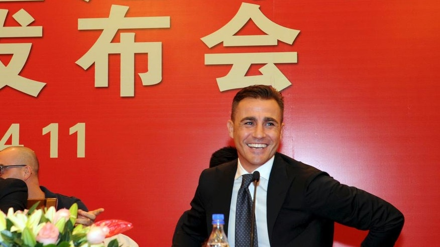 In this Nov. 5, 2014 photo, Italian soccer star Fabio Cannavaro attends a news conference announcing him as the new executive manager of Guangzhou Evergrande Taobao Football Club in Guangzhou in southern China's Guangdong province. The surge of investment in the Chinese Super League not only brings famous foreign players to the country, it increases pressure on the big-name coaches hired to win titles. (Chinatopix Via AP) CHINA OUT