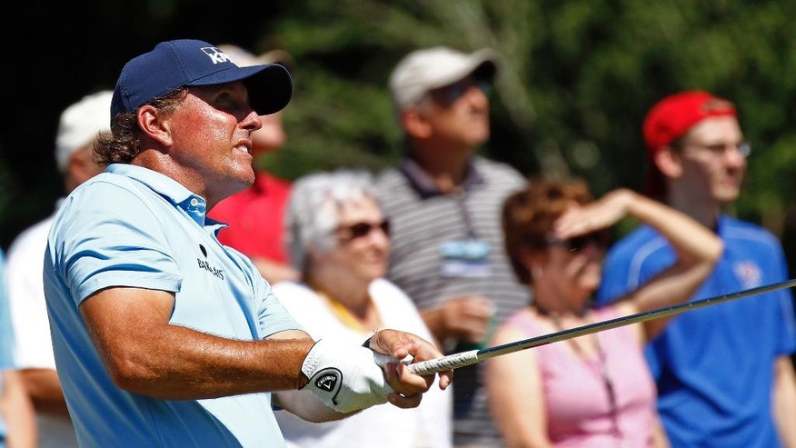 Phil Mickelson watches his tee shot on the 11th tee on the second day of the FedEx St. Jude Classic golf tournament, Friday, June 10, 2016, in Memphis, Tenn. (AP Photo/Rogelio V. Solis)