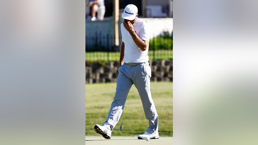 Dustin Johnson reacts to a double bogey on the 18th hole during the second day of the FedEx St. Jude Classic golf tournament, Friday, June 10, 2016, in Memphis, Tenn. (AP Photo/Rogelio V. Solis)
