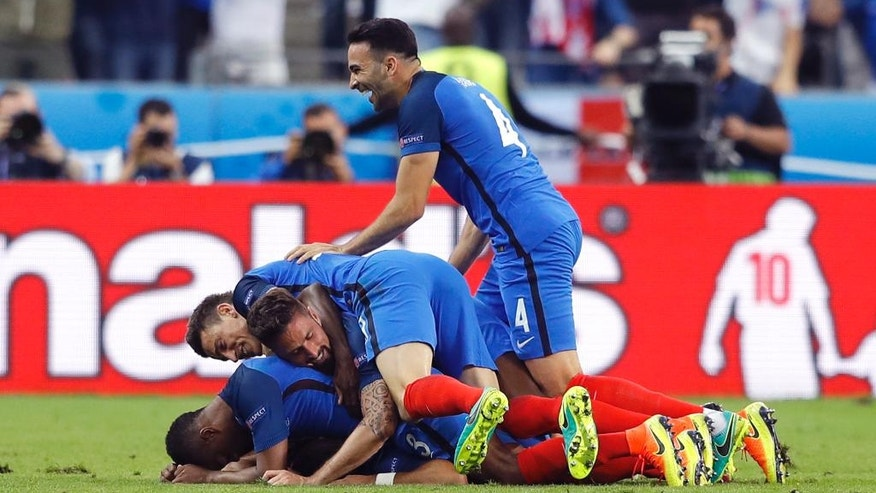 French players celebrate after France's Dimitri Payet scored during the Euro 2016 Group A soccer match between France and Romania, at the Stade de France, in Saint-Denis, north of Paris, Friday, June 10, 2016. (AP Photo/Frank Augstein)