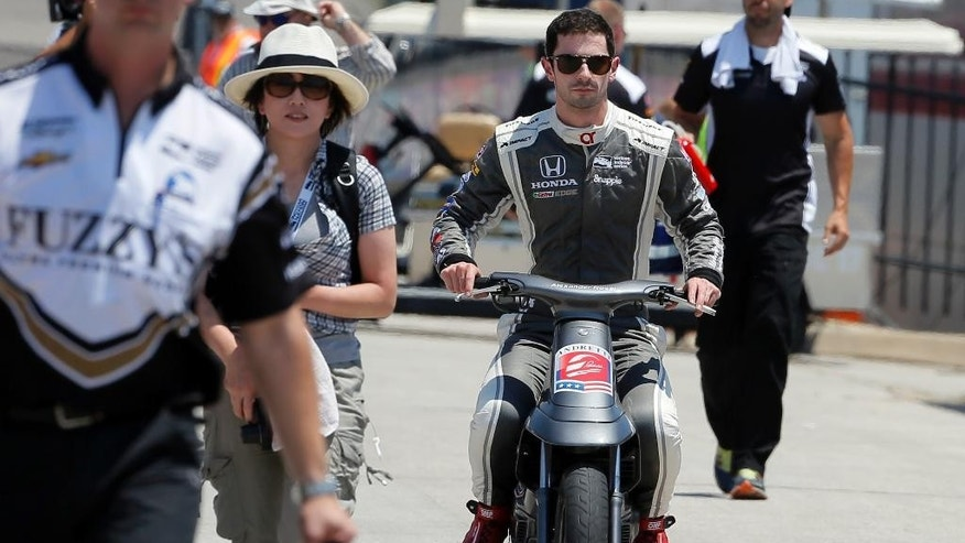 Alexander Rossi drives a scooter off of pit road as he heads to the garage area after a Indycar auto racing practice at Texas Motor Speedway, Friday, June 10, 2016, in Fort Worth, Texas. (AP Photo/Tony Gutierrez)
