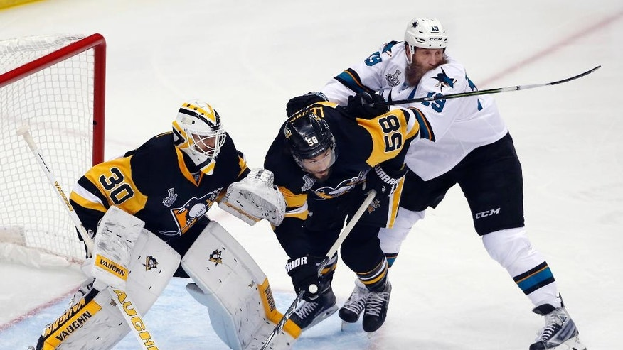 San Jose Sharks' Joe Thornton (19) checks Pittsburgh Penguins' Kris Letang (58) in front of Penguins goalie Matt Murray (30) during the first period in Game 5 of the NHL hockey Stanley Cup Finals on Thursday, June 9, 2016, in Pittsburgh. (AP Photo/Gene J. Puskar)