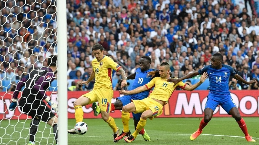 Romania's Bogdan Stancu, 2nd left, attempts a shot at goal during the Euro 2016 Group A soccer match between France and Romania, at the Stade de France, in Saint-Denis, north of Paris, Friday, June 10, 2016. (AP Photo/Martin Meissner)