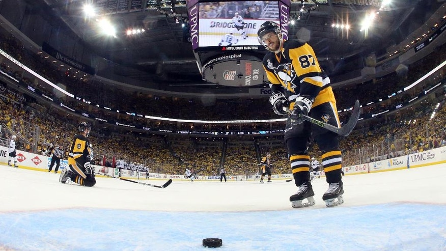Pittsburgh Penguins' Sidney Crosby (87) retrieves the puck after the San Jose Sharks scored an empty-net goal during the third period in Game 5 of the NHL hockey Stanley Cup Finals on Thursday, June 9, 2016, in Pittsburgh. The Sharks won 4-2. (Bruce Bennett/Pool Photo via AP)