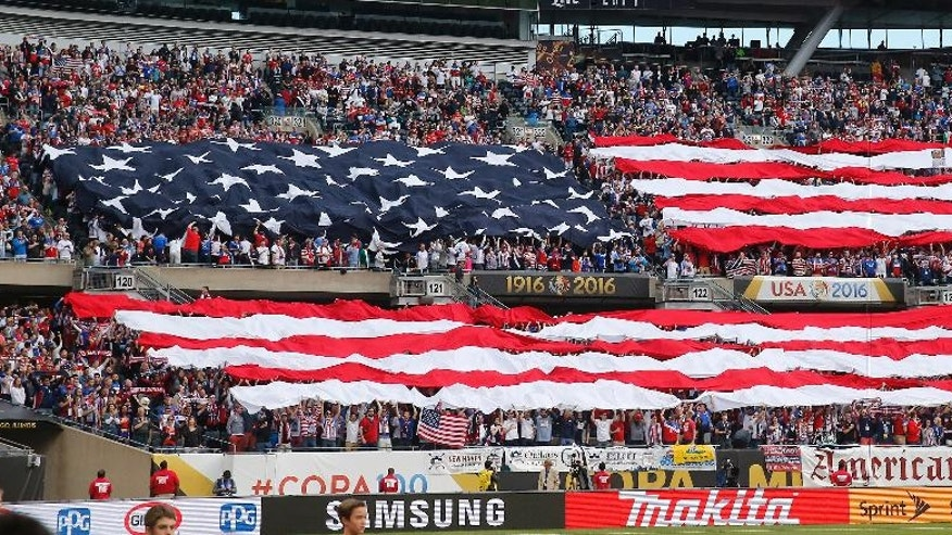 FILE - In this June 7, 2016, file photo, United States fans display the American flag during the national anthem before a Copa America Centenario group A soccer match between the United States and Costa Rica, at Soldier Field in Chicago. American soccer fans can watch a quintuple-header of major international tournament matches Saturday, the first of six in the next week-and-a-half. (AP Photo/Charles Rex Arbogast, File)