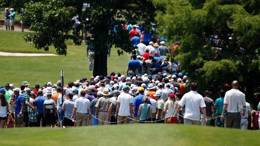 Fans rush the walkway to follow the pairing of Phil Mickelson and Brett Stegmaier on their way down the No. 1 fairway on the third round of the FedEx St. Jude Classic Golf Tournament, Saturday, June 11, 2016, in Memphis, Tenn. (AP Photo/Rogelio V. Solis)