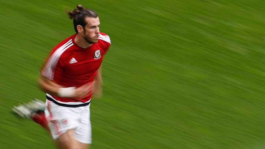 In this photo taken with slow shutter speed, Wales's Gareth Bale warms up prior the Euro 2016 Group B soccer match between Wales and Slovakia, at the Nouveau stadium in Bordeaux, France, Saturday, June 11, 2016. (AP Photo/Hassan Ammar)