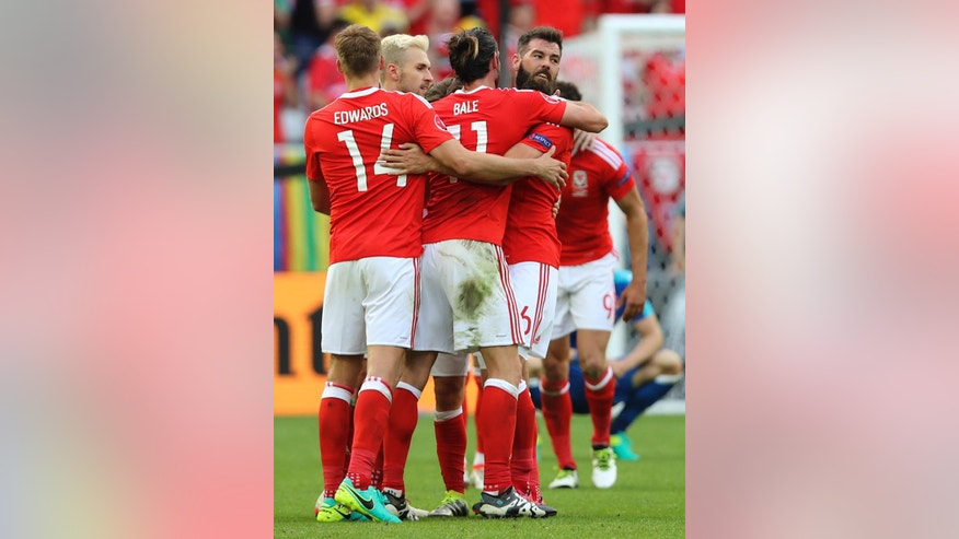 Welsh players celebrate at the end of the Euro 2016 Group B soccer match between Wales and Slovakia, at the Nouveau stadium in Bordeaux, France, Saturday, June 11, 2016. Wales won 2-1. (AP Photo/Andrew Medichini)