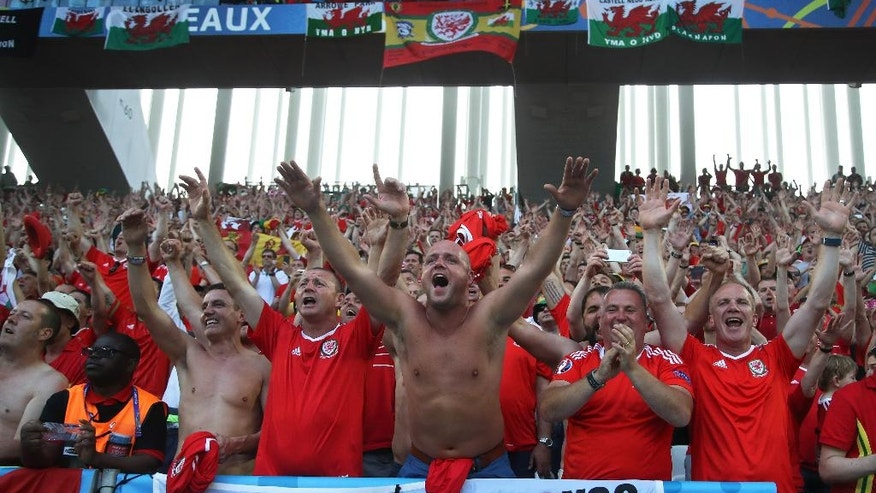Wales supporters celebrate at the end of the Euro 2016 Group B soccer match between Wales and Slovakia, at the Nouveau stadium in Bordeaux, France, Saturday, June 11, 2016. (AP Photo/Petr David Josek)