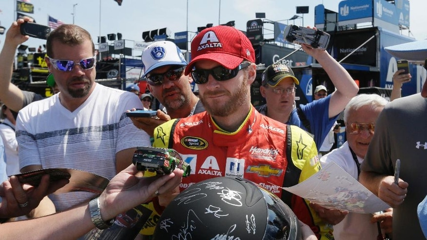 Fans surround driver Dale Earnhardt Jr. seeking autographs before a practice session for the NASCAR Sprint Cup series auto race at Michigan International Speedway, Saturday, June 11, 2016 in Brooklyn, Mich. (AP Photo/Carlos Osorio)