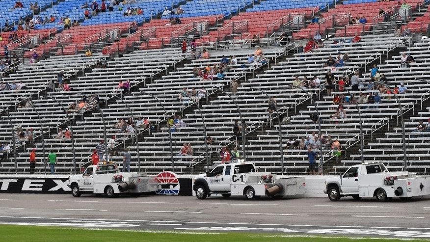 Dryers move along the front stretch after a rain shower before an IndyCar auto race at Texas Motor Speedway, Saturday, June 11, 2016, in Fort Worth, Texas. (AP Photo/Larry Papke)