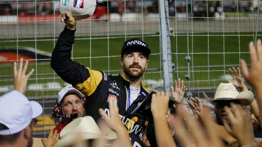 James Hinchcliffe prepares to toss out a signed cap to fans in the stands as he and other drivers greeted people and signed autographs during a rain delay at the IndyCar auto race at Texas Motor Speedway, Saturday, June 11, 2016, in Fort Worth, Texas. The race was postponed until Sunday. (AP Photo/Tony Gutierrez)