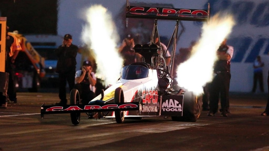 In this photo provided by NHRA, Steve Torrence drives in Top Fuel qualifying Friday, June 10, 2016, for the NHRA Summernationals drag races at Old Bridge Township Raceway Park in Englightown, N.J. Torrence took the provisional top spot with a run at to a 3.735 seconds at 325.06 mph. (Randy Anderson/NHRA via AP)