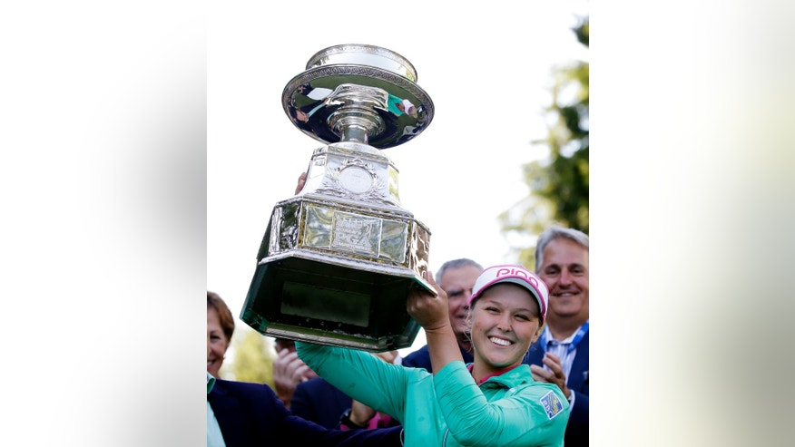 Brooke Henderson, of Canada, lifts the championship trophy after winning the Women's PGA Championship golf tournament at Sahalee Country Club on Sunday, June 12, 2016, in Sammamish, Wash. (AP Photo/Elaine Thompson)