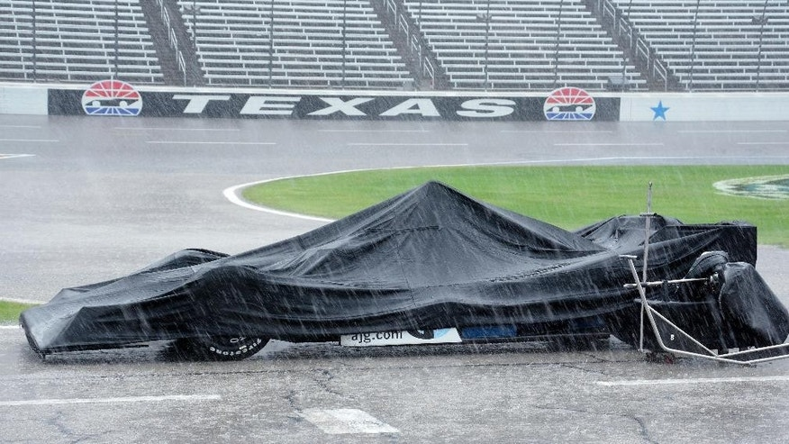 The race car of Max Chilton, from England, is covered by a tarp during a thunderstorm which stopped an IndyCar auto race at Texas Motor Speedway, Sunday, June 12, 2016, in Fort Worth, Texas. (AP Photo/Larry Papke)